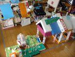 幼稚園。周りにはみんなの家があります。園庭には動くブランコも!