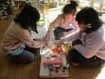 ケーキ屋さんに、それぞれのお家からお客さんがやってきました。小さな人形を動かしながら、自分たちの作ったものを使って仲間とのやりとりを楽しんでいます